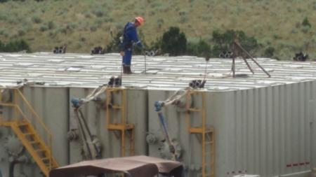Oil field technician gauging a flowback tank. Workers check such tanks several times an hour, during which many are exposed to potentially dangerous amounts of the carcinogen benzene. (NIOSH)