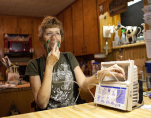 Lynn Buehring wears a respirator outdoors to keep from becoming overwhelmed by the fumes that envelop her home
